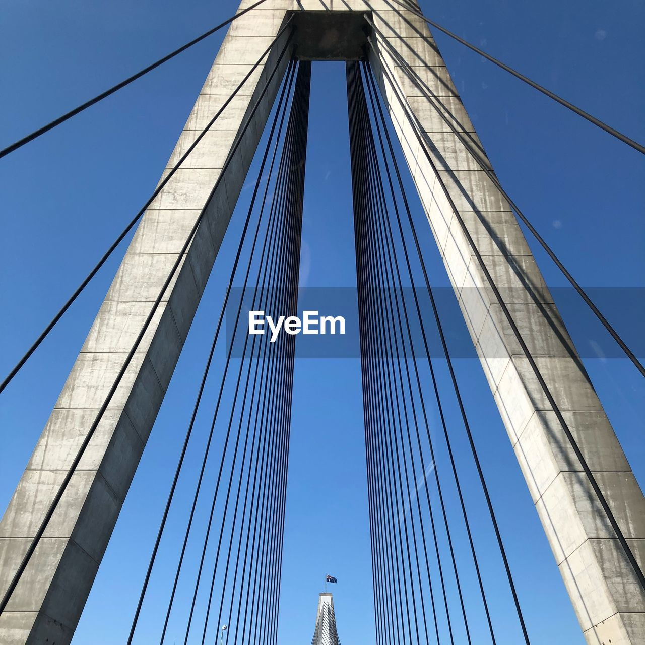sky, connection, low angle view, bridge - man made structure, built structure, architecture, engineering, bridge, cable-stayed bridge, cable, suspension bridge, blue, transportation, steel cable, clear sky, travel destinations, nature, tourism, day, outdoors