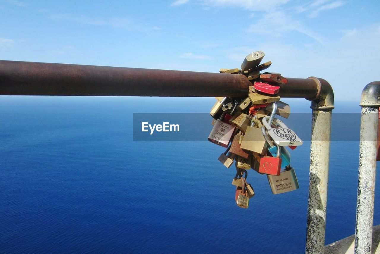 Love Padlocks Handing On Railing Against Blue Sea