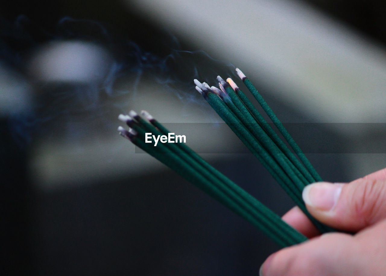 Cropped hands of person holding burning incense sticks