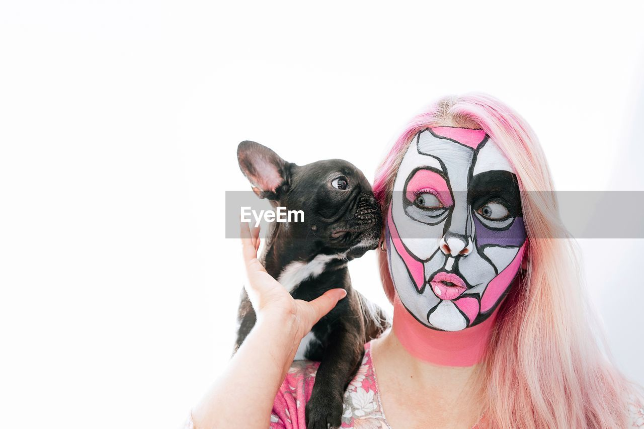 Close-Up Of Face Painted Woman Holding Puppy Against White Background