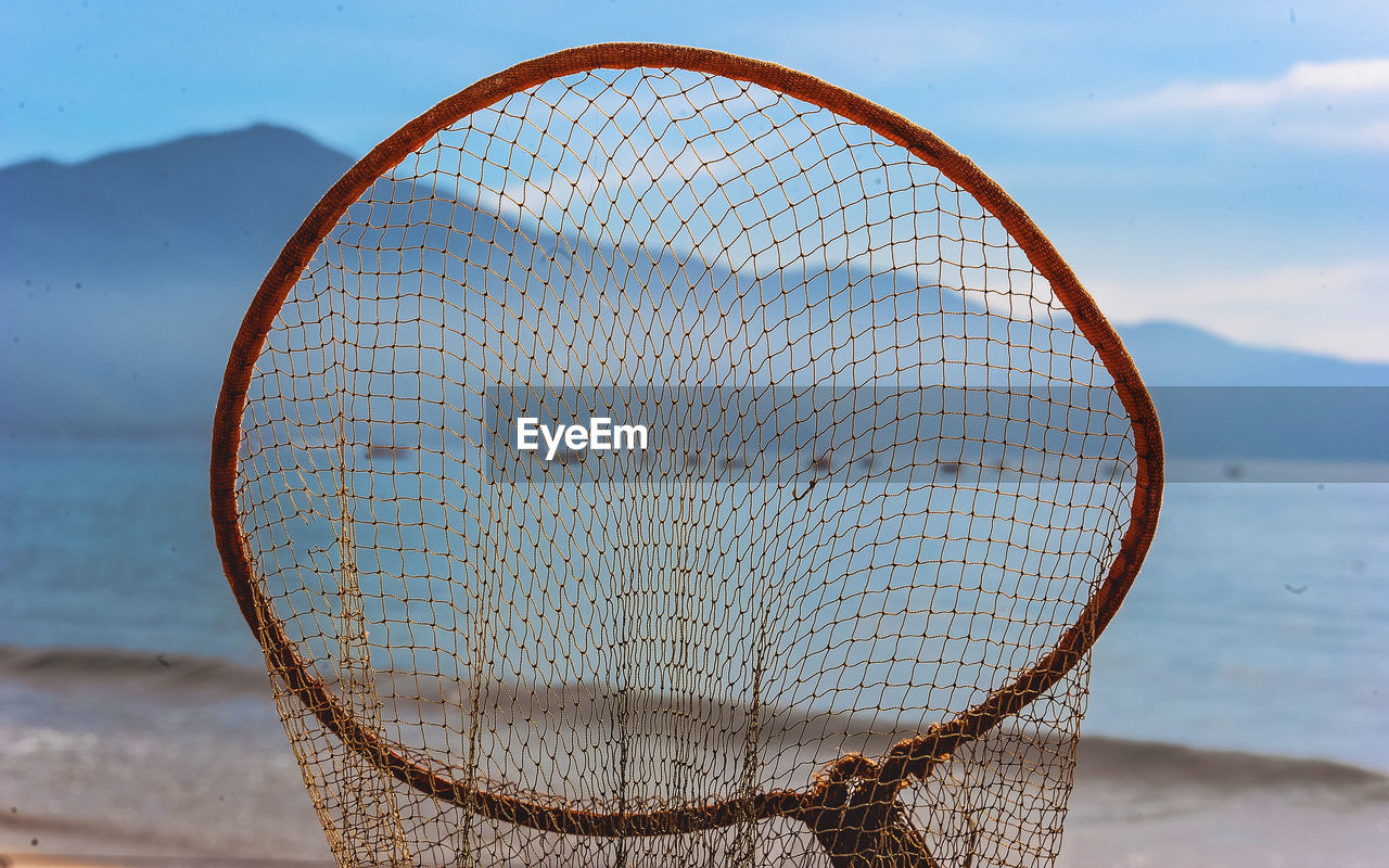 CLOSE-UP OF FISHING NET ON SHORE