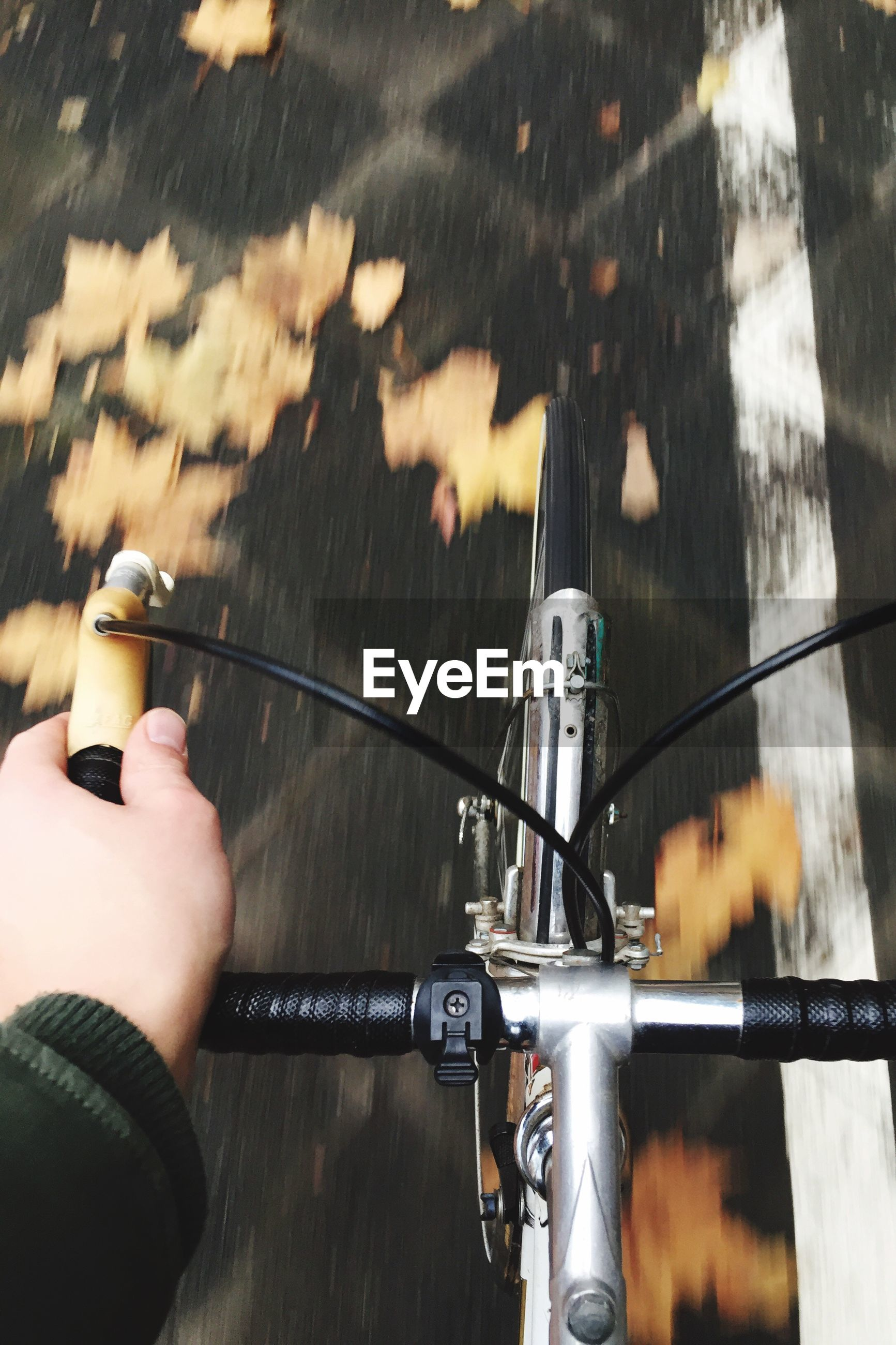 CLOSE-UP OF HAND HOLDING BICYCLE ON METAL
