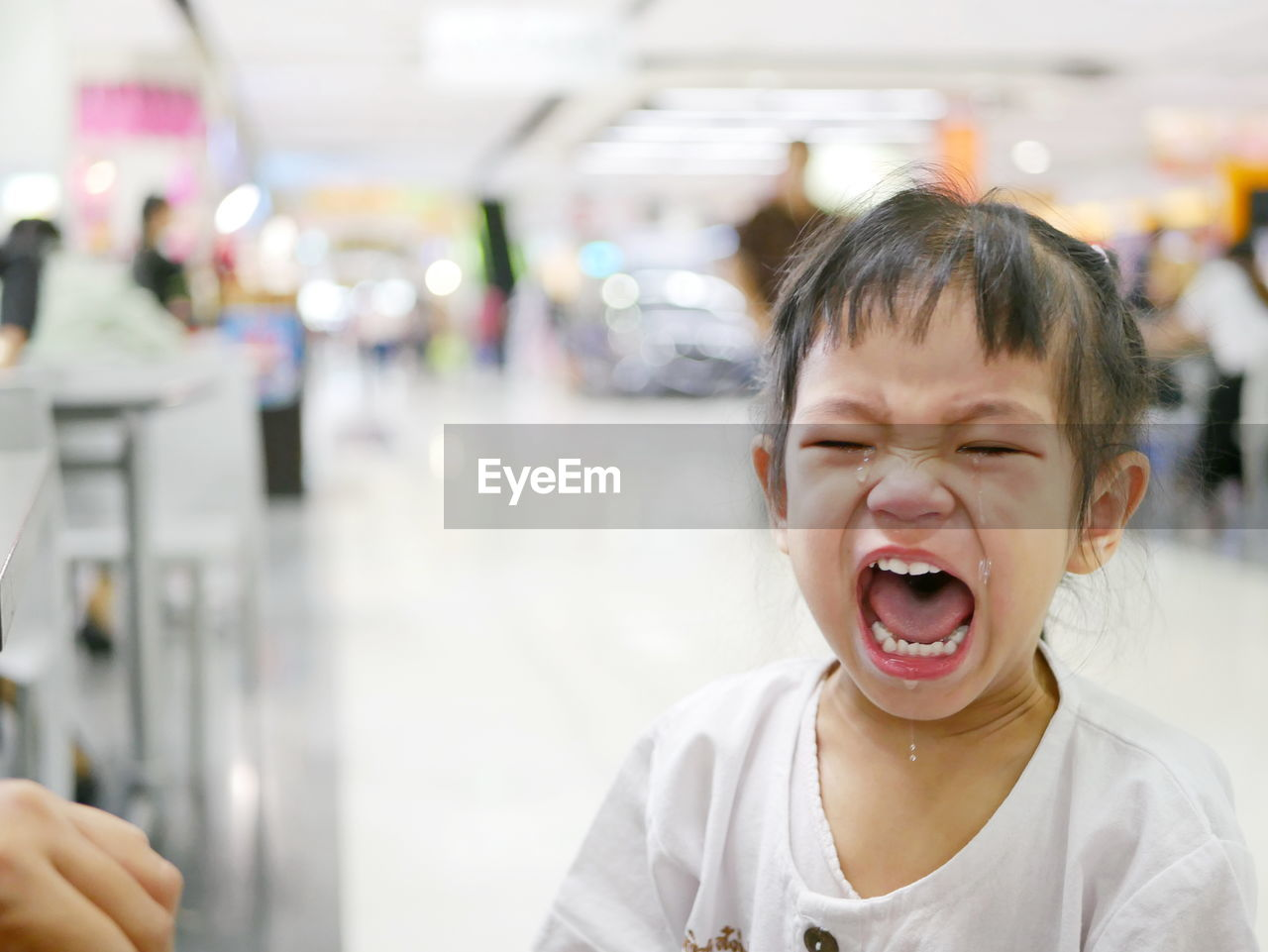 Close-Up Of Girl Crying In Shopping Mall