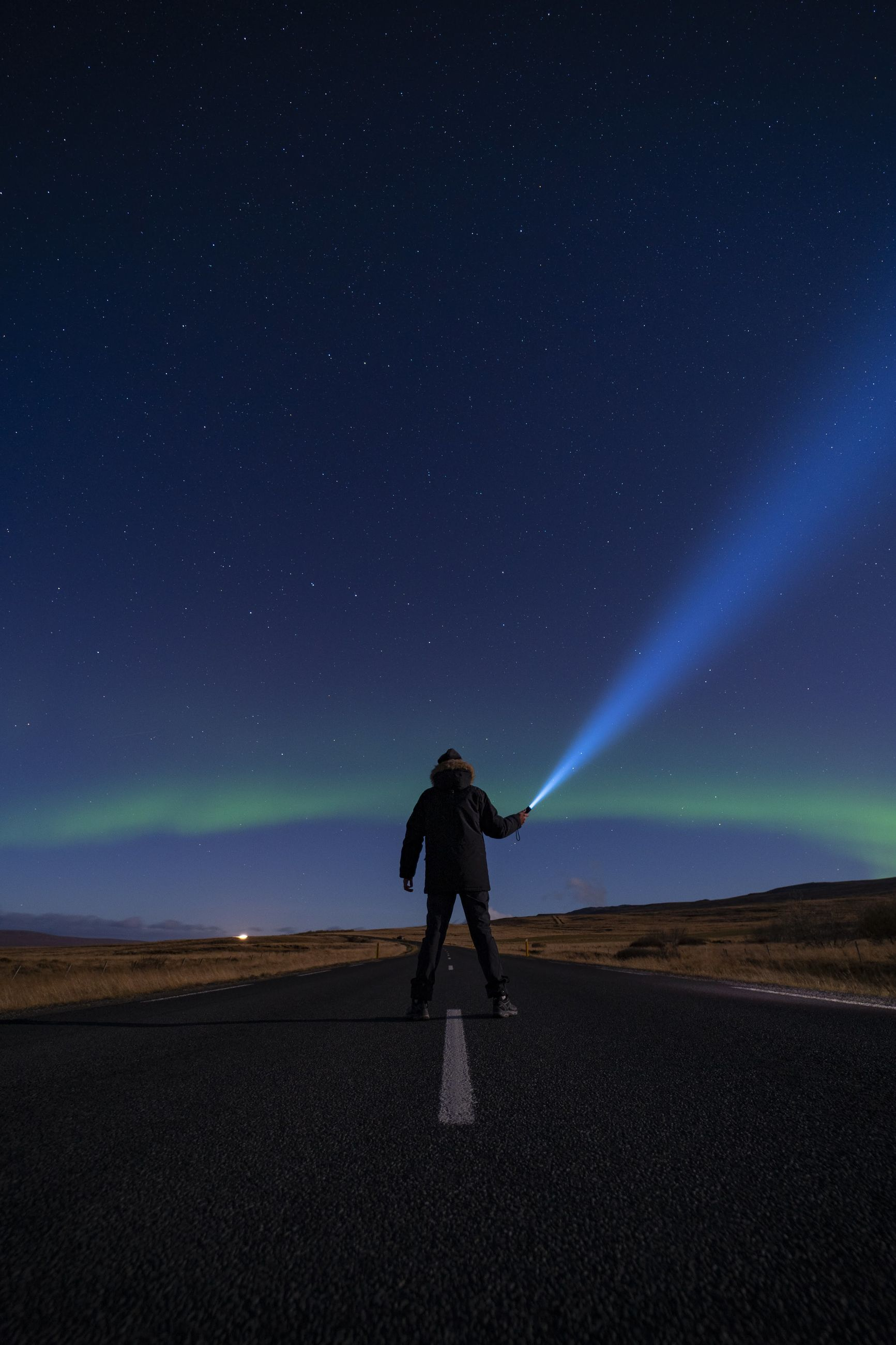Rear view of man holding illuminated flashlight while standing on road against sky at night