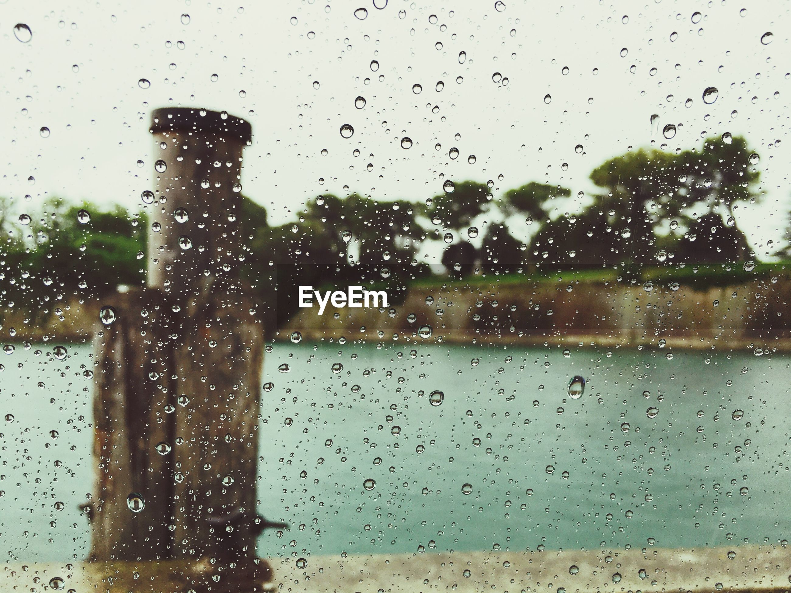 Wooden post in river against sky seen through wet glass window during monsoon