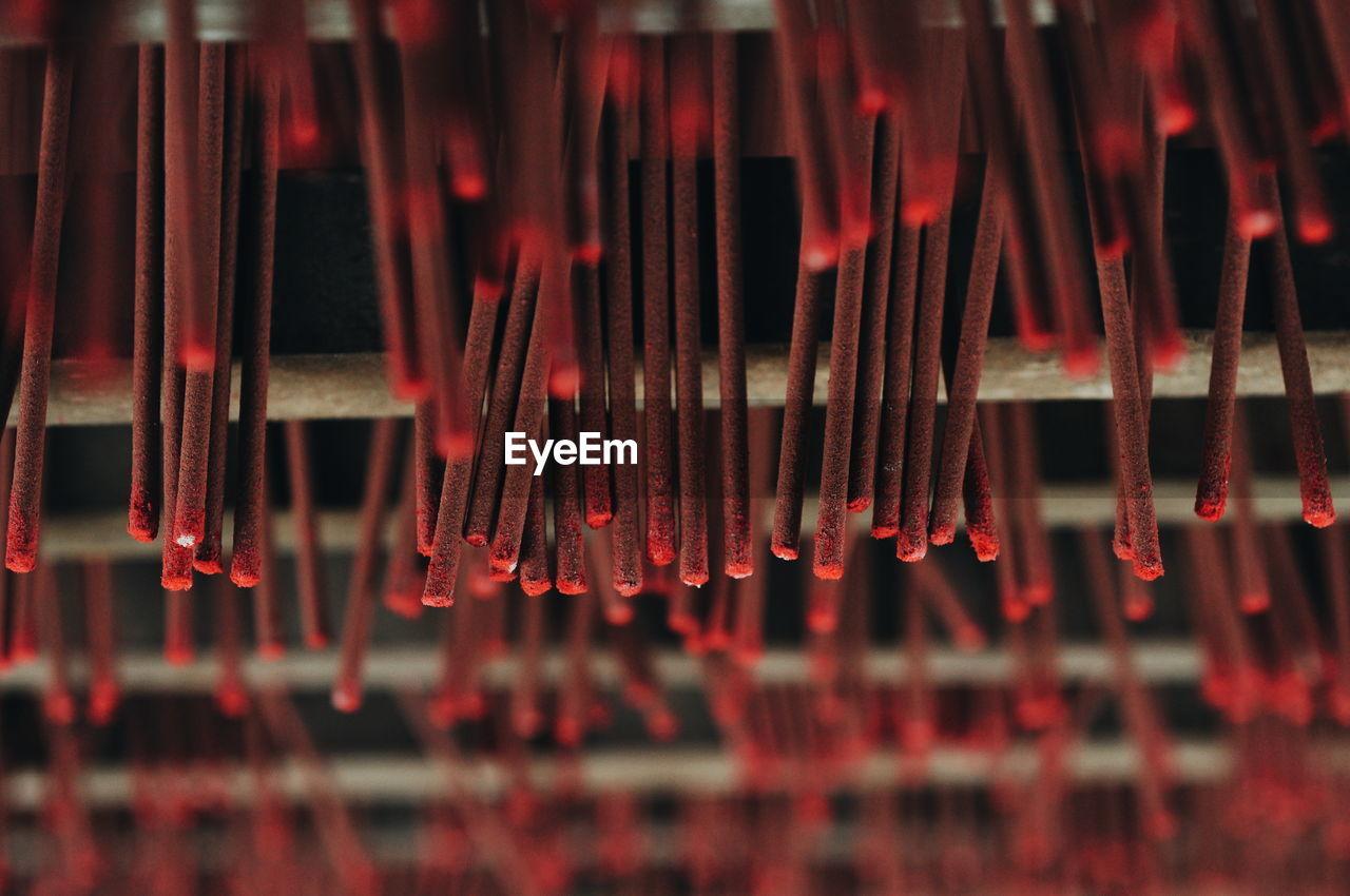 Full frame shot of red incense sticks hanging