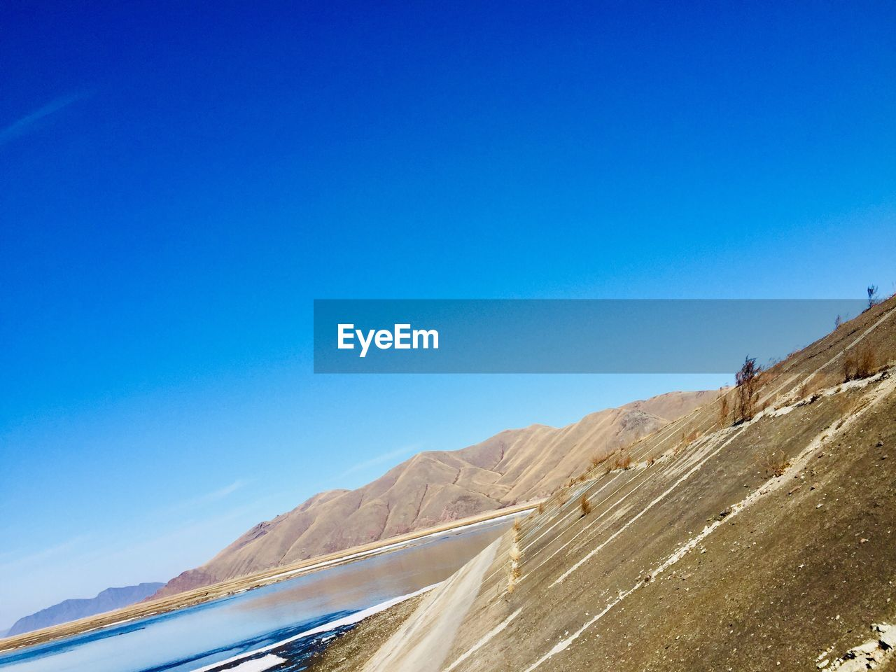 sky, blue, copy space, scenics - nature, clear sky, beauty in nature, nature, no people, tranquil scene, day, mountain, tranquility, transportation, non-urban scene, land, sunlight, road, water, outdoors, idyllic, climate, arid climate
