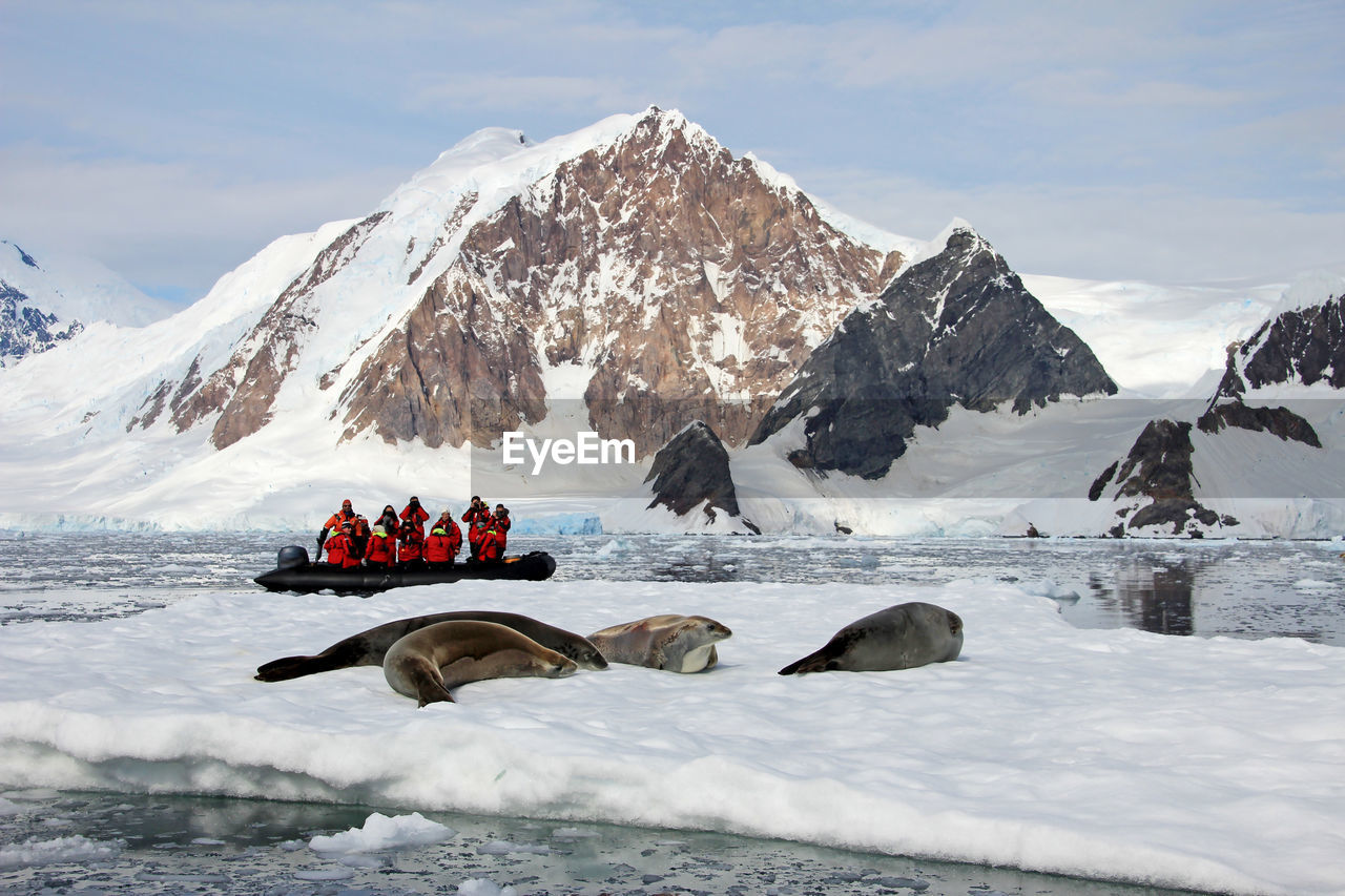 People in inflatable raft on sea by snowcapped mountain during winter