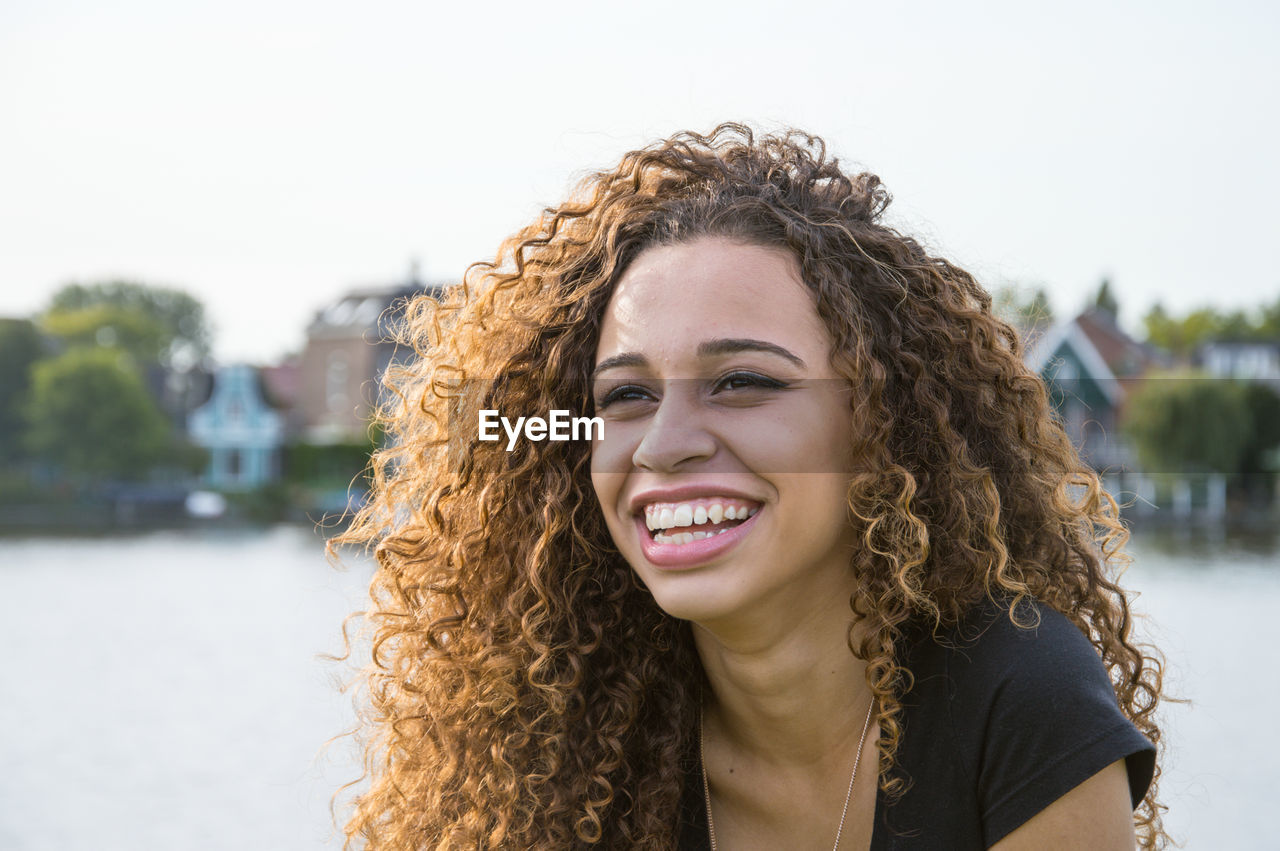 Portrait Of Smiling Teenage Girl With Curly Hair