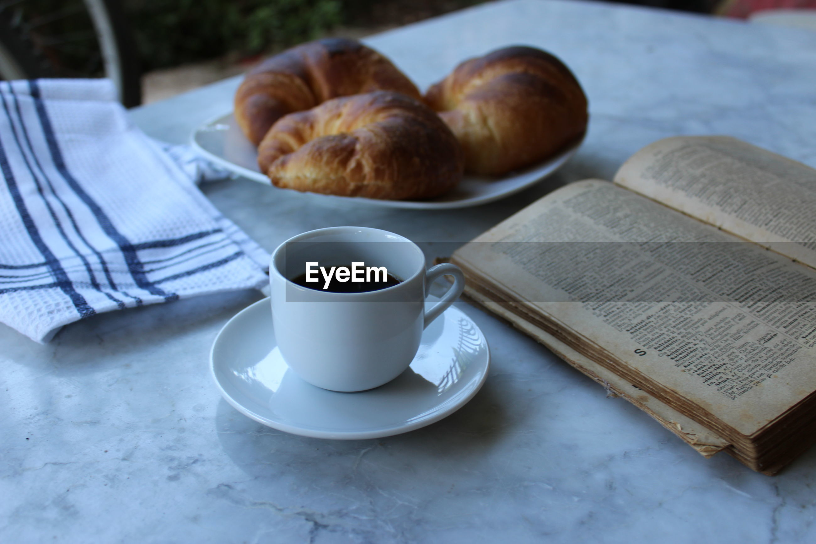 Croissants with coffee and book on table