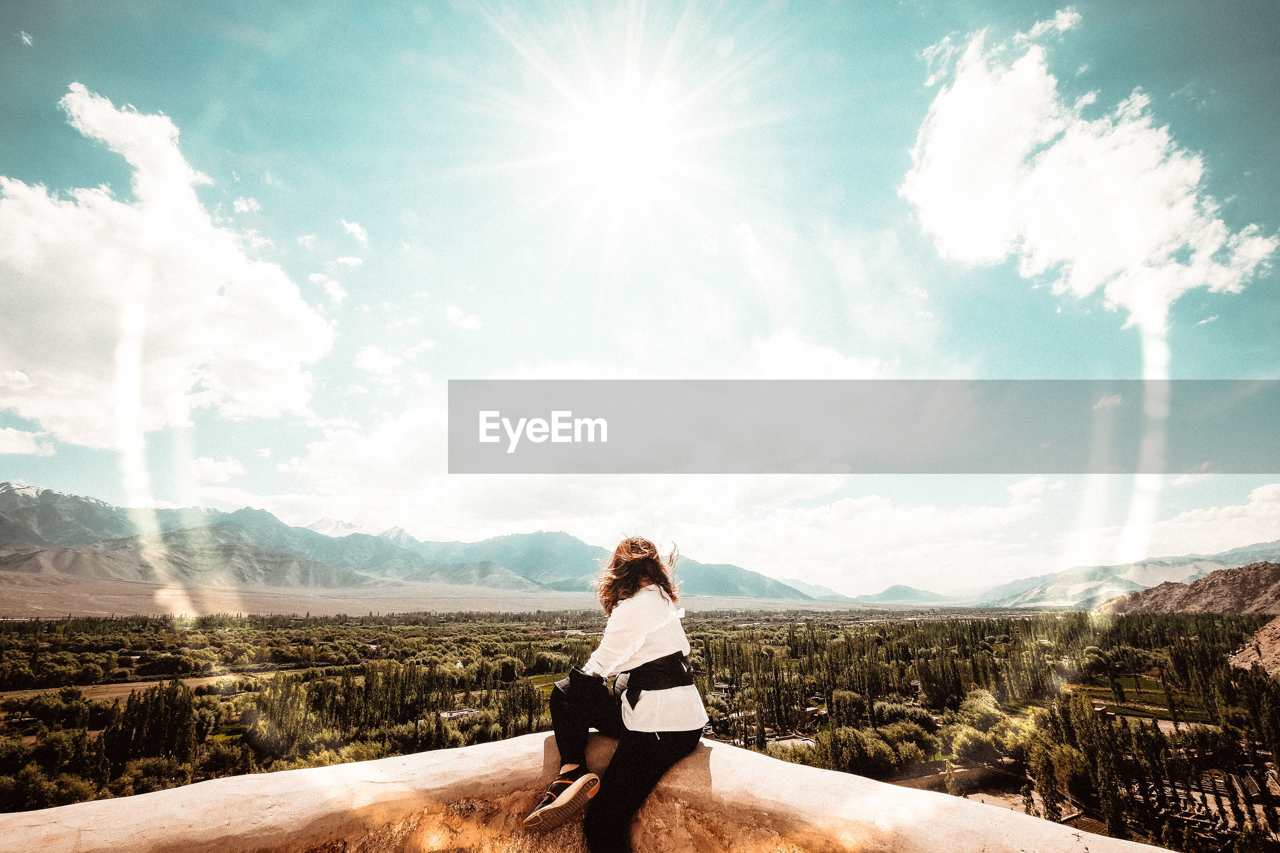 Side view of woman looking at landscape while sitting against sky on sunny day