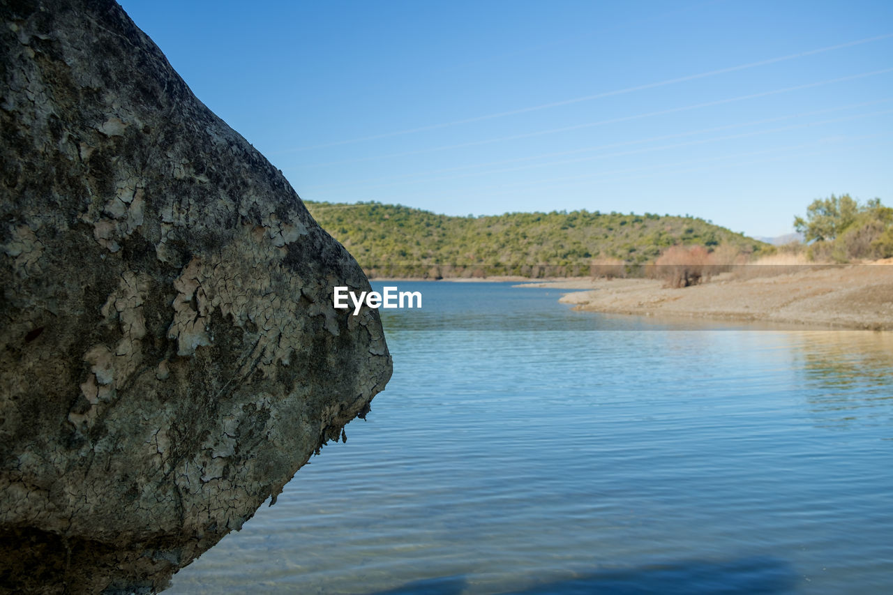 sky, water, nature, scenics - nature, tranquility, beauty in nature, rock, tranquil scene, day, non-urban scene, no people, rock - object, blue, land, tree, solid, rock formation, plant, mountain, outdoors