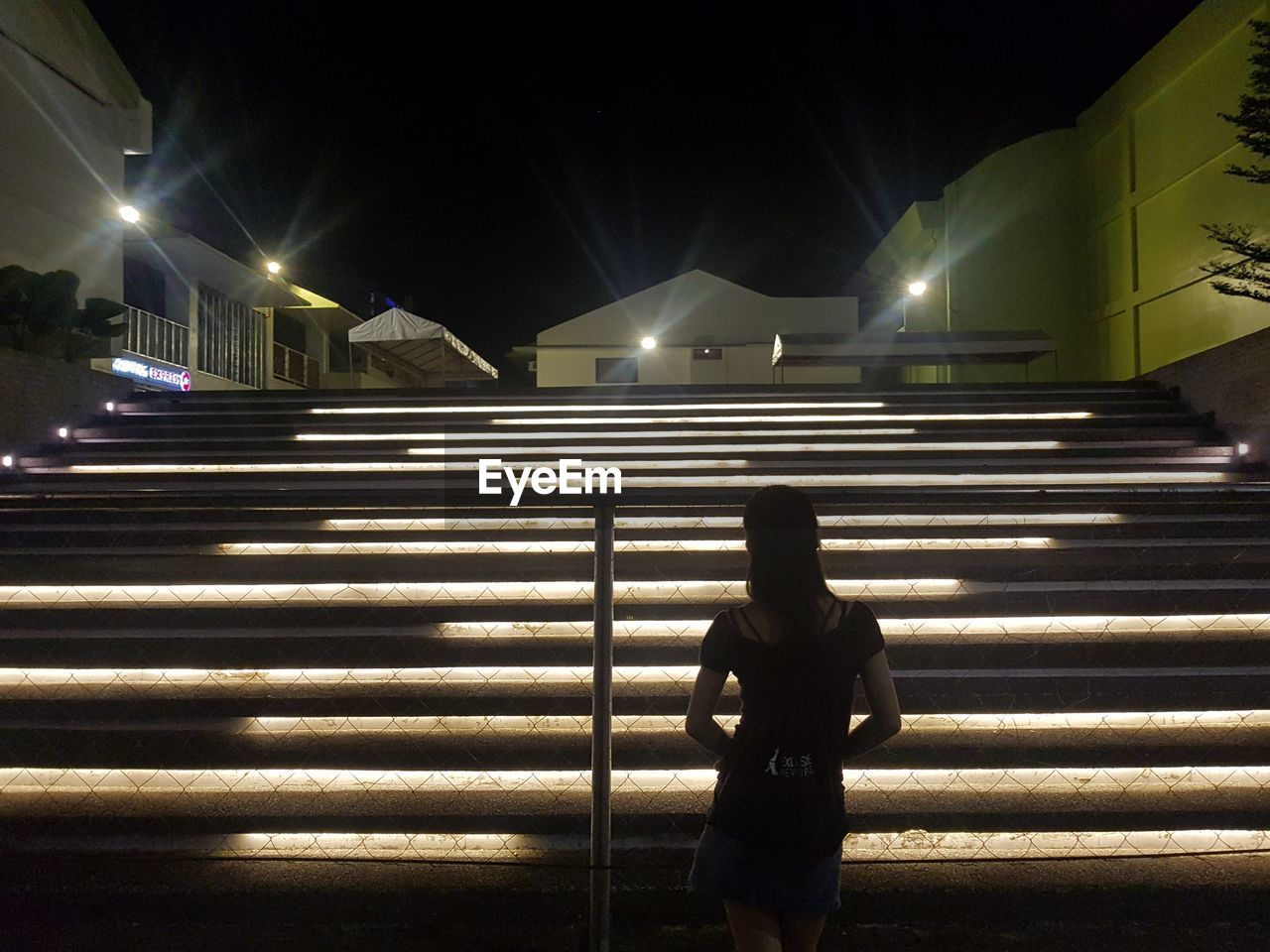 illuminated, night, real people, one person, street, architecture, city, lighting equipment, street light, road, nature, rear view, three quarter length, transportation, lifestyles, standing, light - natural phenomenon, leisure activity, outdoors