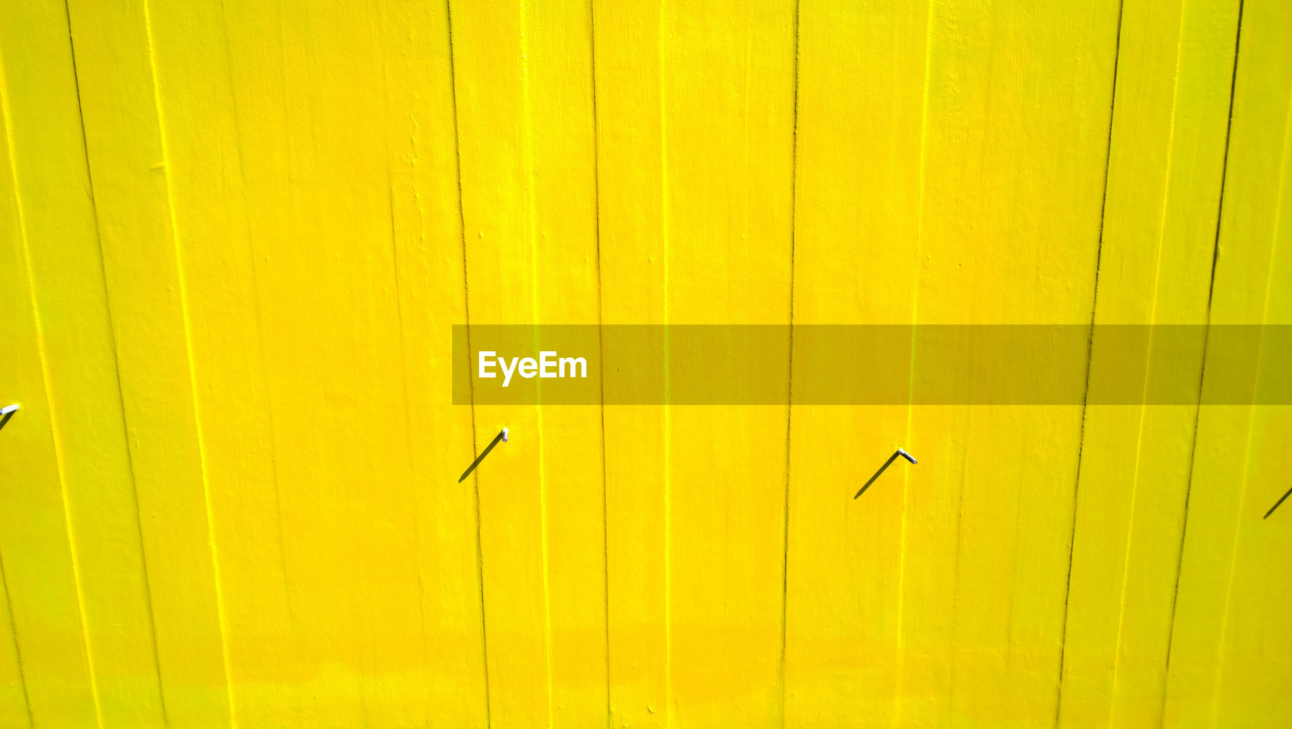 Nails on yellow wall during sunny day