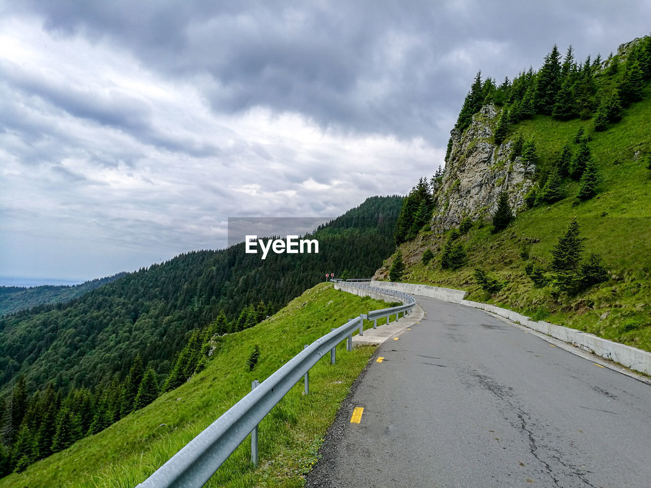 road, cloud - sky, sky, the way forward, mountain, transportation, scenics, tree, nature, day, tranquility, green color, no people, mountain road, outdoors, tranquil scene, mountain range, winding road, beauty in nature, landscape, grass