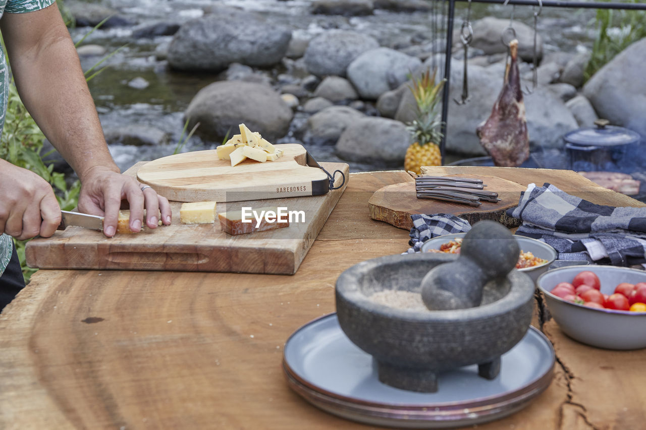 MIDSECTION OF PERSON PREPARING FOOD AT TABLE