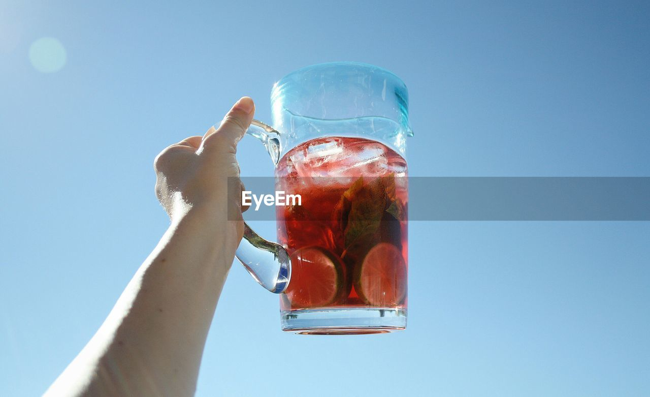 Cropped Image Of Person Holding Drink Against Clear Blue Sky On Sunny Day
