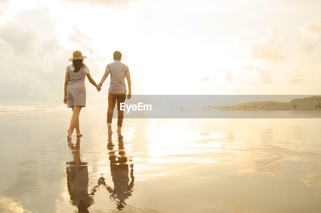 Rear View Of Couple Walking At Beach Against Cloudy Sky During Sunset