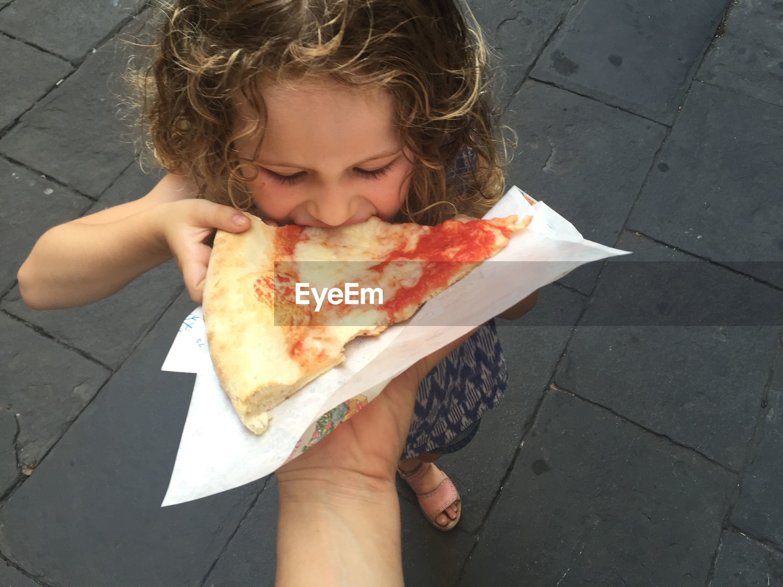 Cropped hand of parent feeding pizza slice daughter on street
