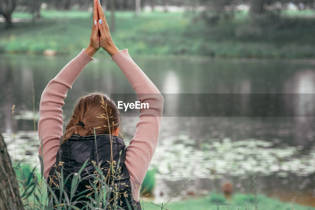 Young woman practicing yoga in park. mental health, wellness and reconnecting with nature concept.