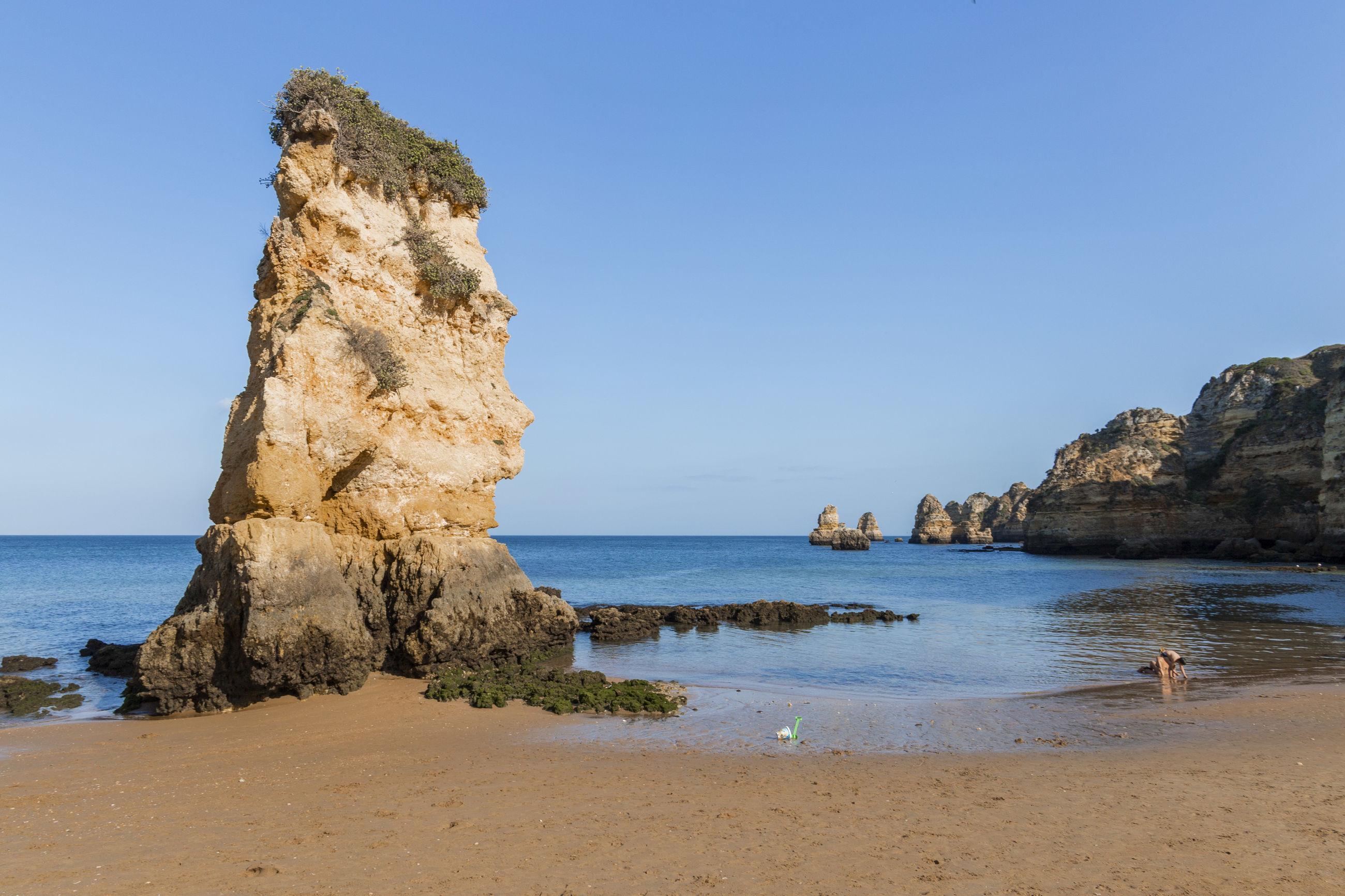 Rock formation on beach against clear blue sky