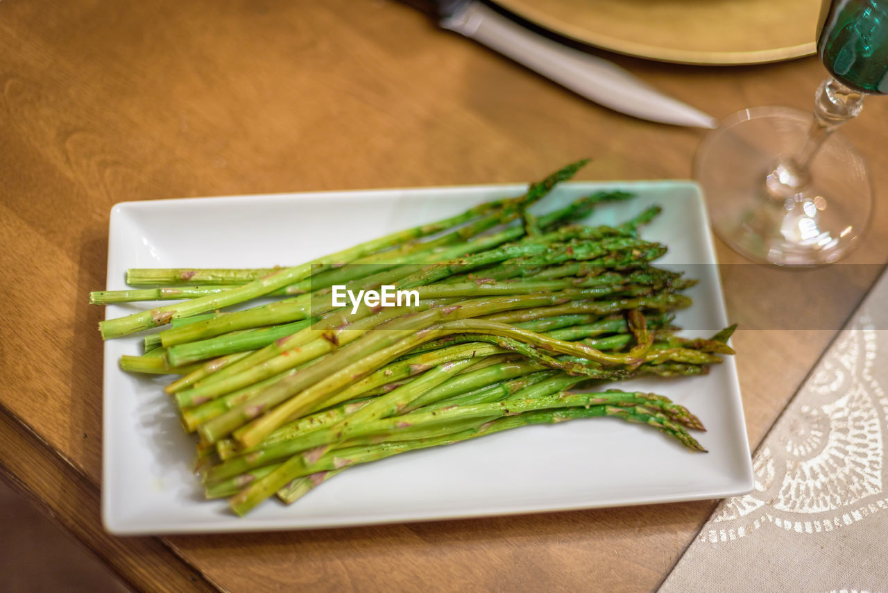 table, food and drink, food, freshness, indoors, still life, green color, vegetable, no people, plate, wellbeing, healthy eating, focus on foreground, high angle view, close-up, asparagus, household equipment, kitchen utensil, eating utensil, wood - material, glass, tray