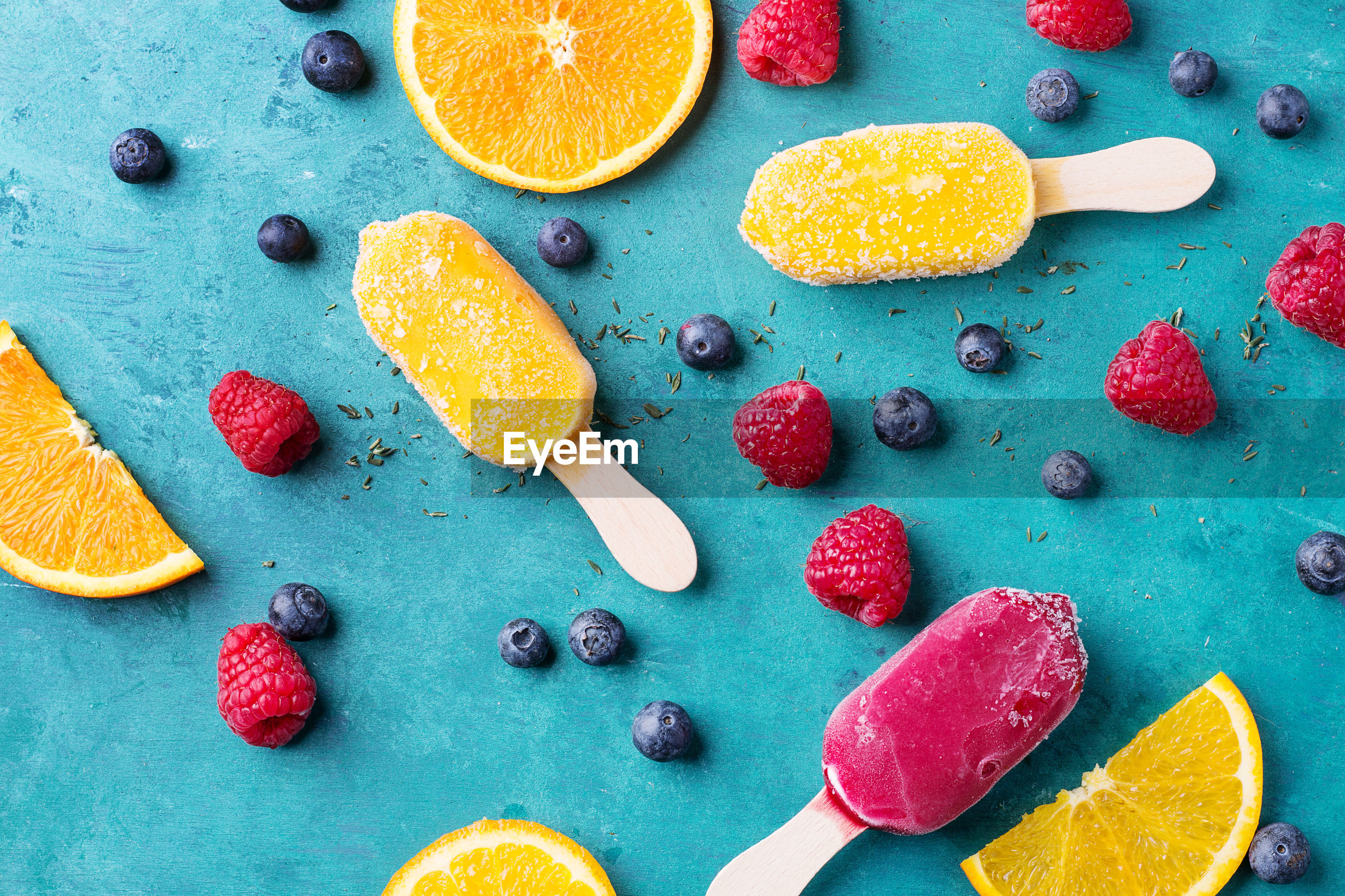 Directly above shot of fruits and ice creams on blue table
