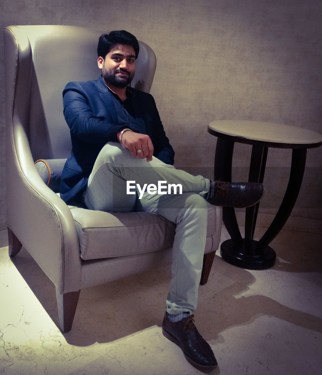 chair, seat, sitting, full length, one person, indoors, young men, real people, young adult, men, front view, males, well-dressed, relaxation, leisure activity, furniture, businessman, business person, armchair