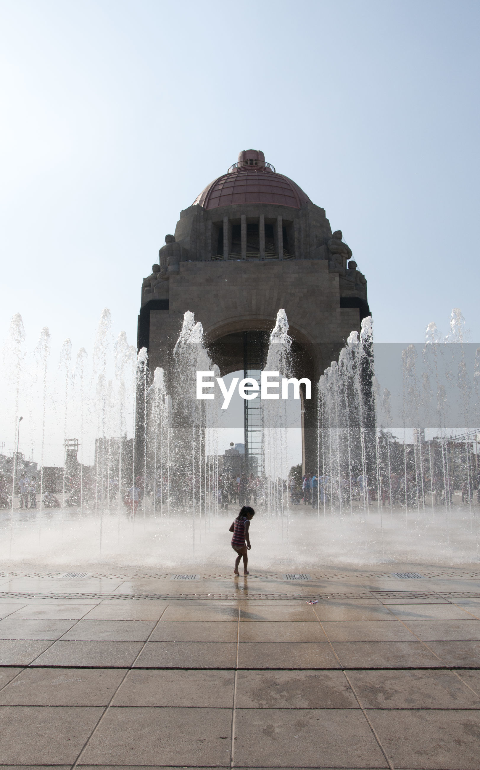 Girl standing by fountain in city against clear sky