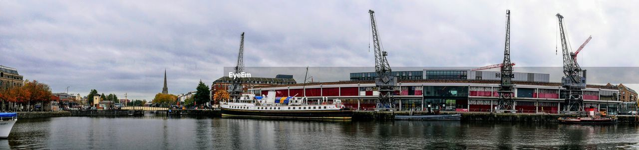 water, nautical vessel, sky, waterfront, mode of transportation, cloud - sky, transportation, built structure, building exterior, architecture, day, no people, industry, nature, river, outdoors, travel, crane - construction machinery, city, passenger craft, sailboat