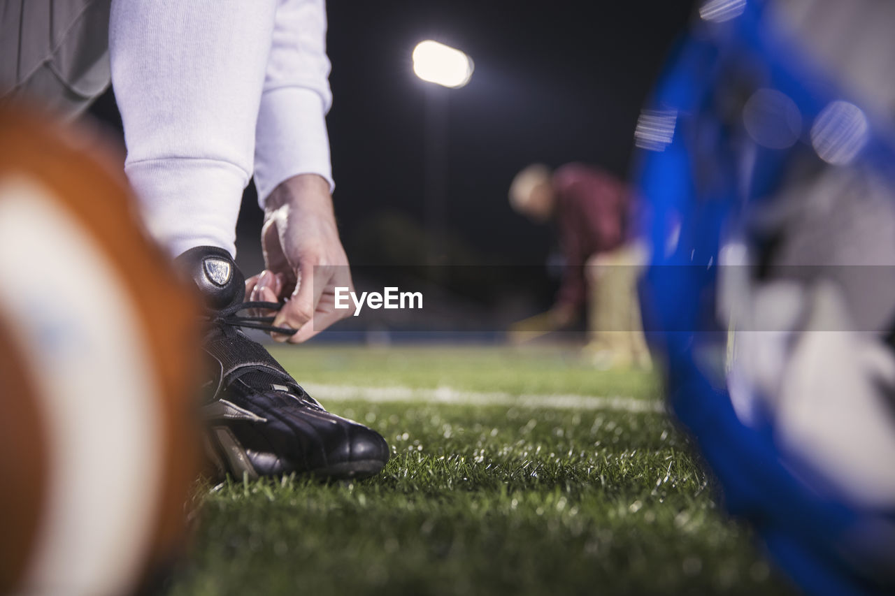 selective focus, real people, low section, human leg, body part, human body part, sport, grass, men, people, night, shoe, illuminated, lifestyles, team sport, ball, leisure activity, soccer, close-up, group of people, human limb, human foot