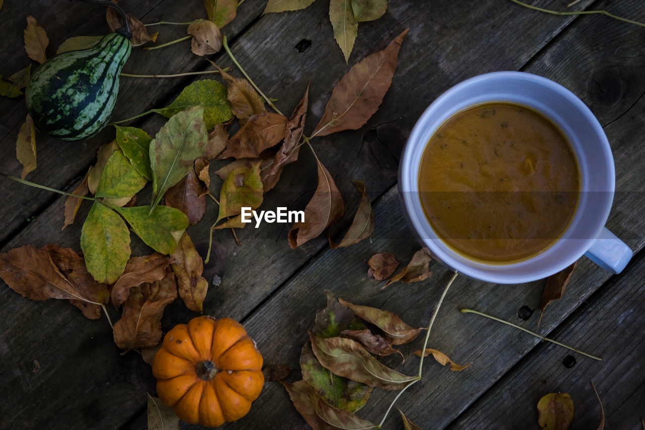 High angle view of soup and leaves on wooden table