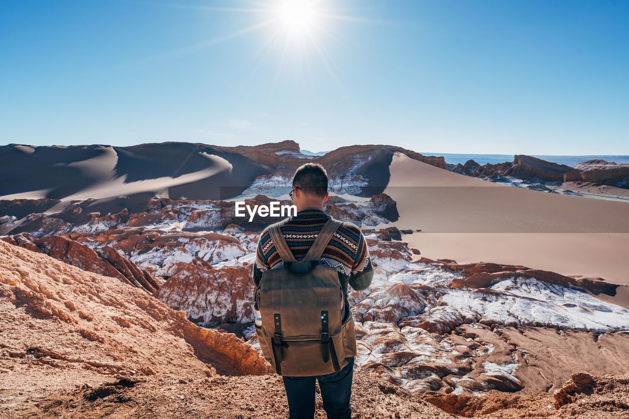 Rear View Of Young Man With Backpack Standing On Mountain Against Clear Sky