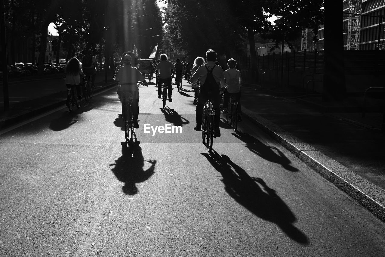 bicycle, transportation, sunlight, real people, shadow, cycling, riding, street, road, land vehicle, mode of transport, men, tree, outdoors, large group of people, lifestyles, leisure activity, day, city, healthy lifestyle, full length, nature, building exterior, architecture, skateboard park, people, adult