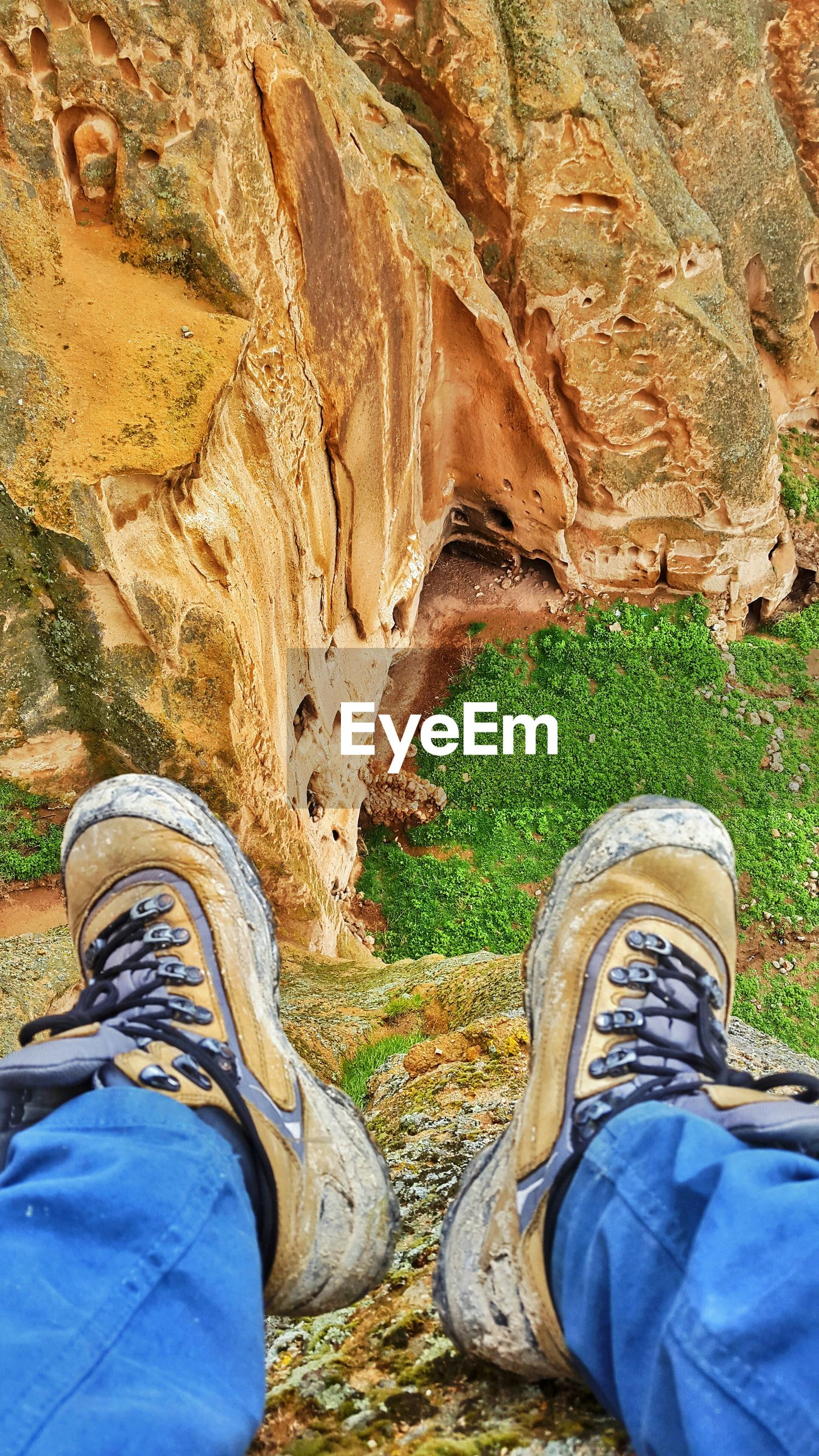 low section, shoe, person, personal perspective, jeans, lifestyles, men, leisure activity, standing, casual clothing, field, footwear, human foot, unrecognizable person, grass, outdoors, day