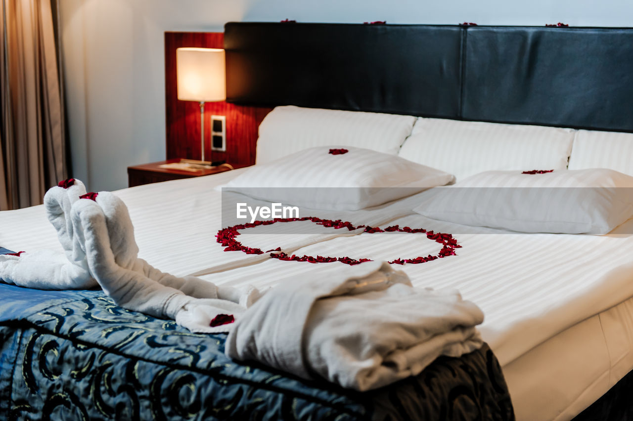 High Angle View Of Red Flower Petals On Bed In Hotel Room
