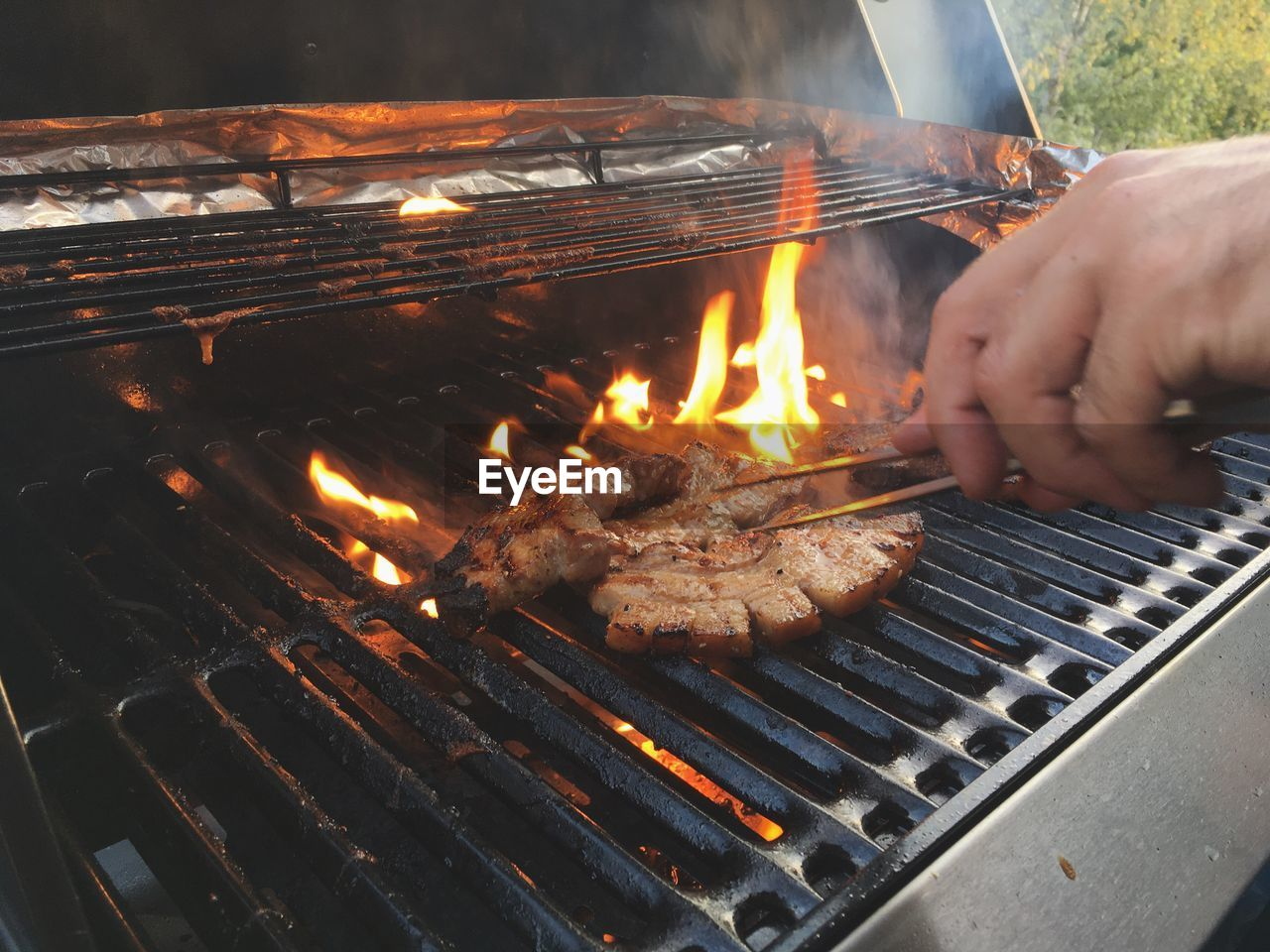 barbecue, barbecue grill, grilled, heat - temperature, meat, food and drink, real people, flame, food, human hand, one person, burning, preparation, outdoors, coal, human body part, preparing food, leisure activity, sausage, men, day, freshness, fire pit, close-up