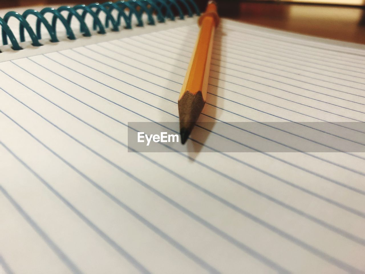 Close-up of pencil with note pad on table