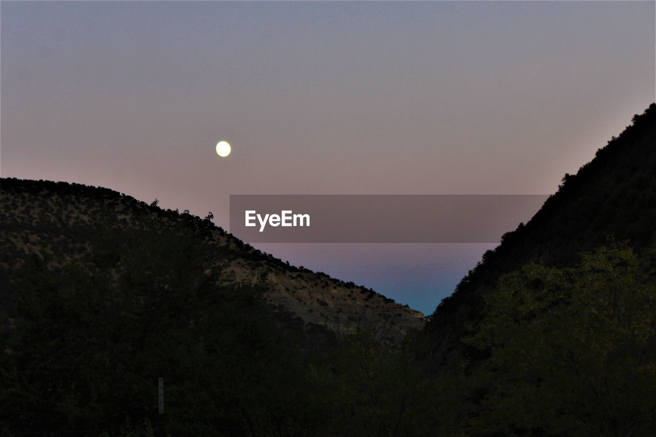 moon, beauty in nature, nature, tranquil scene, mountain, scenics, tranquility, sky, no people, outdoors, low angle view, silhouette, sunset, tree, landscape, clear sky, astronomy, day