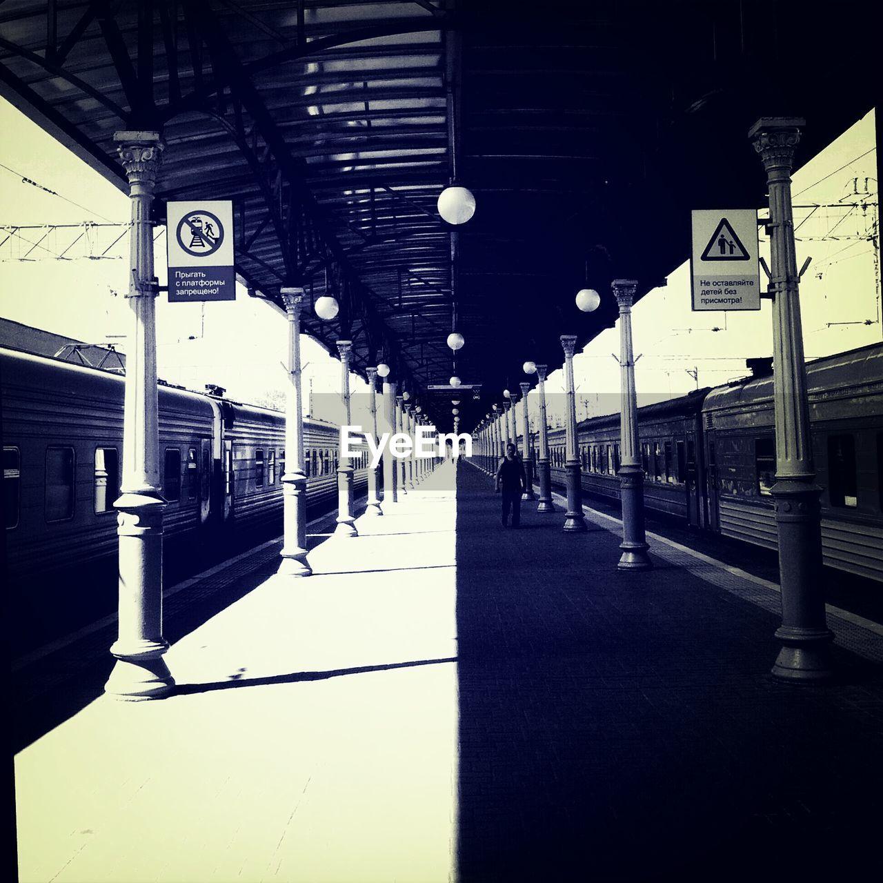 Man Walking On Railroad Station Platform On Sunny Day