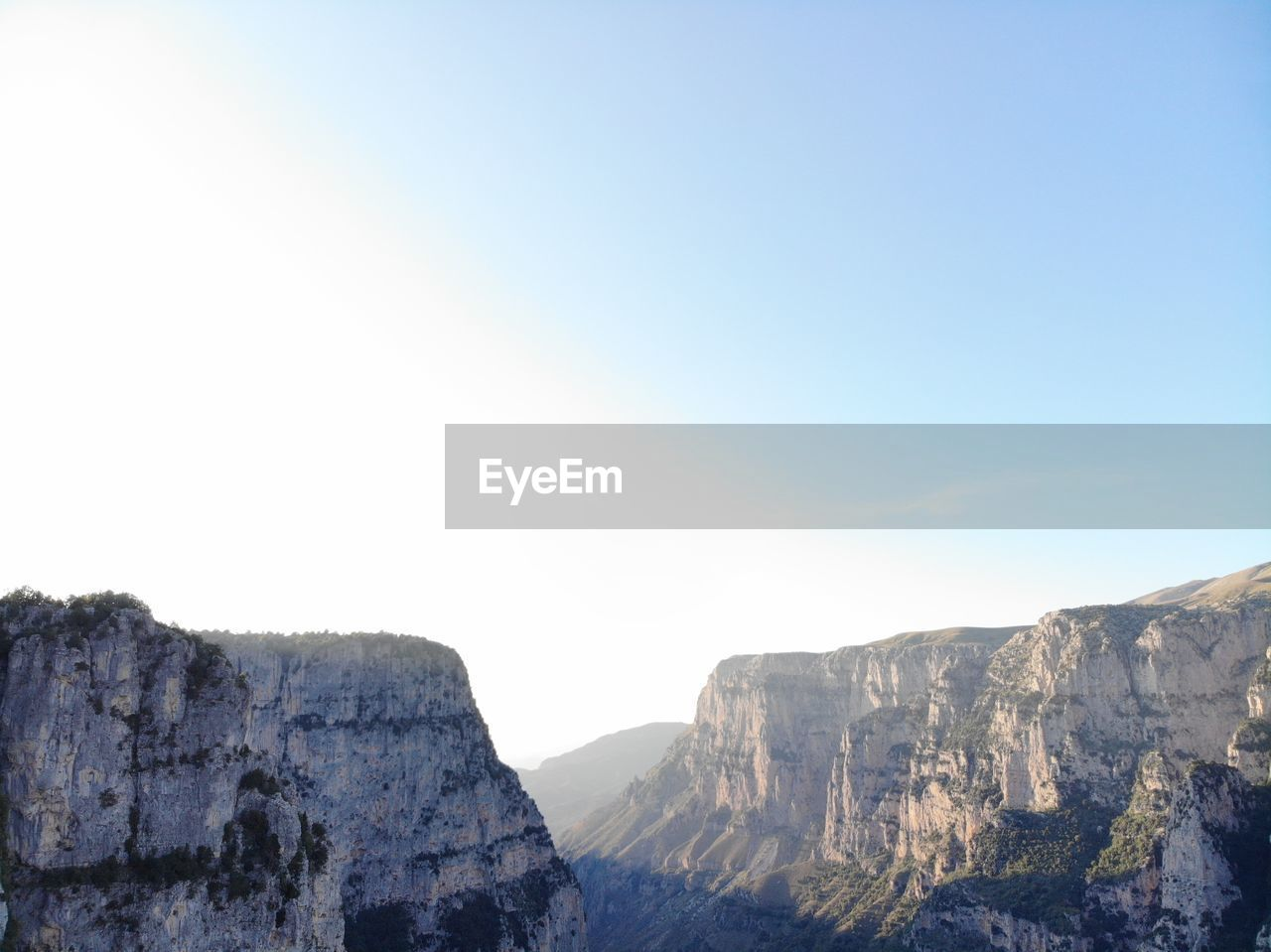 sky, mountain, rock, beauty in nature, nature, scenics - nature, tranquility, copy space, tranquil scene, environment, formation, mountain range, landscape, cliff, clear sky, no people, non-urban scene, rocky mountains, day, rock formation, outdoors, mountain peak, high, height, eroded