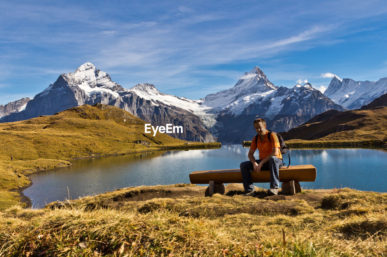 sitting, one person, mountain, leisure activity, real people, full length, nature, water, beauty in nature, adult, lifestyles, scenics - nature, seat, bench, sky, idyllic, lake, mountain range, outdoors, snowcapped mountain