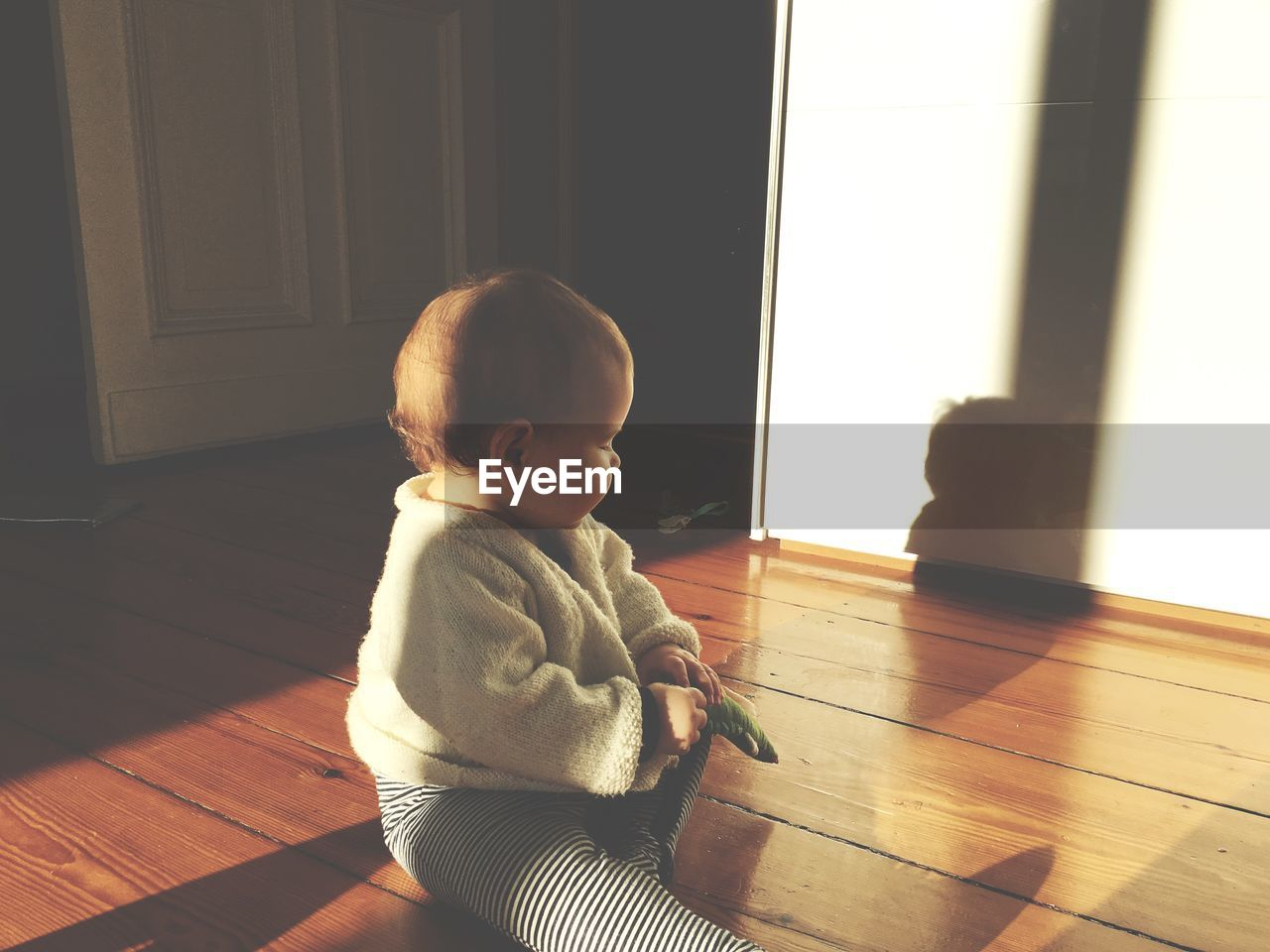 indoors, baby, hardwood floor, one person, innocence, childhood, babyhood, toddler, home interior, real people, cute, sunlight, shadow, sitting, day, babies only, people