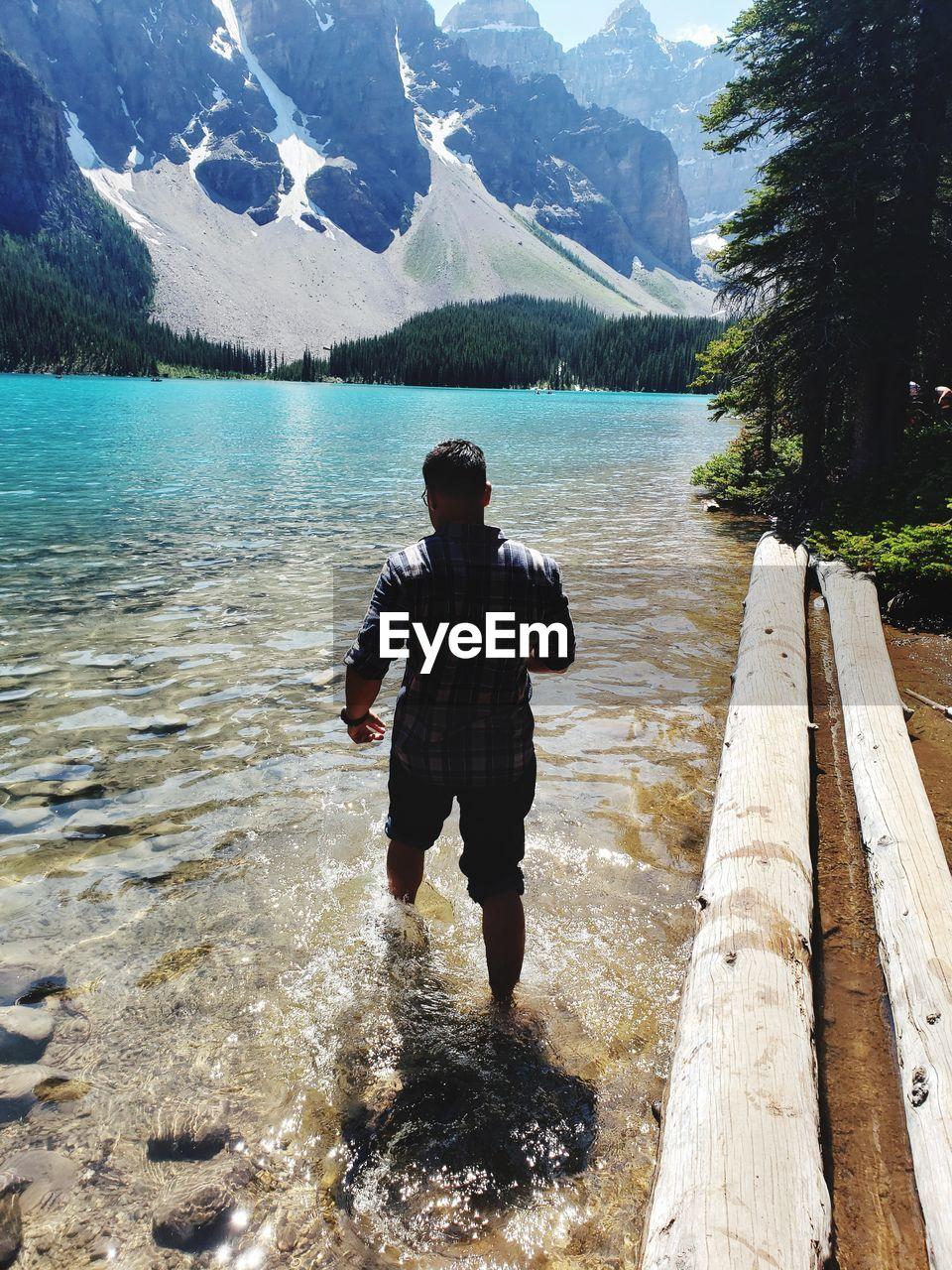 REAR VIEW OF MAN ON LAKE