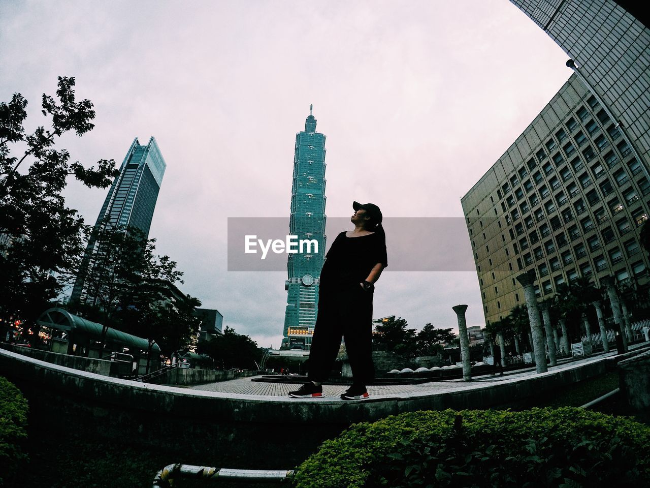 architecture, built structure, building exterior, city, skyscraper, modern, full length, cityscape, travel destinations, outdoors, standing, real people, sky, day, men, one person, urban skyline, tree, young adult, people