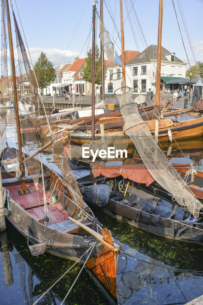mode of transportation, nautical vessel, day, transportation, moored, water, sky, nature, no people, architecture, pole, sailboat, mast, outdoors, built structure, building exterior, sunlight, harbor, reflection, fishing industry, fishing boat, port, marina