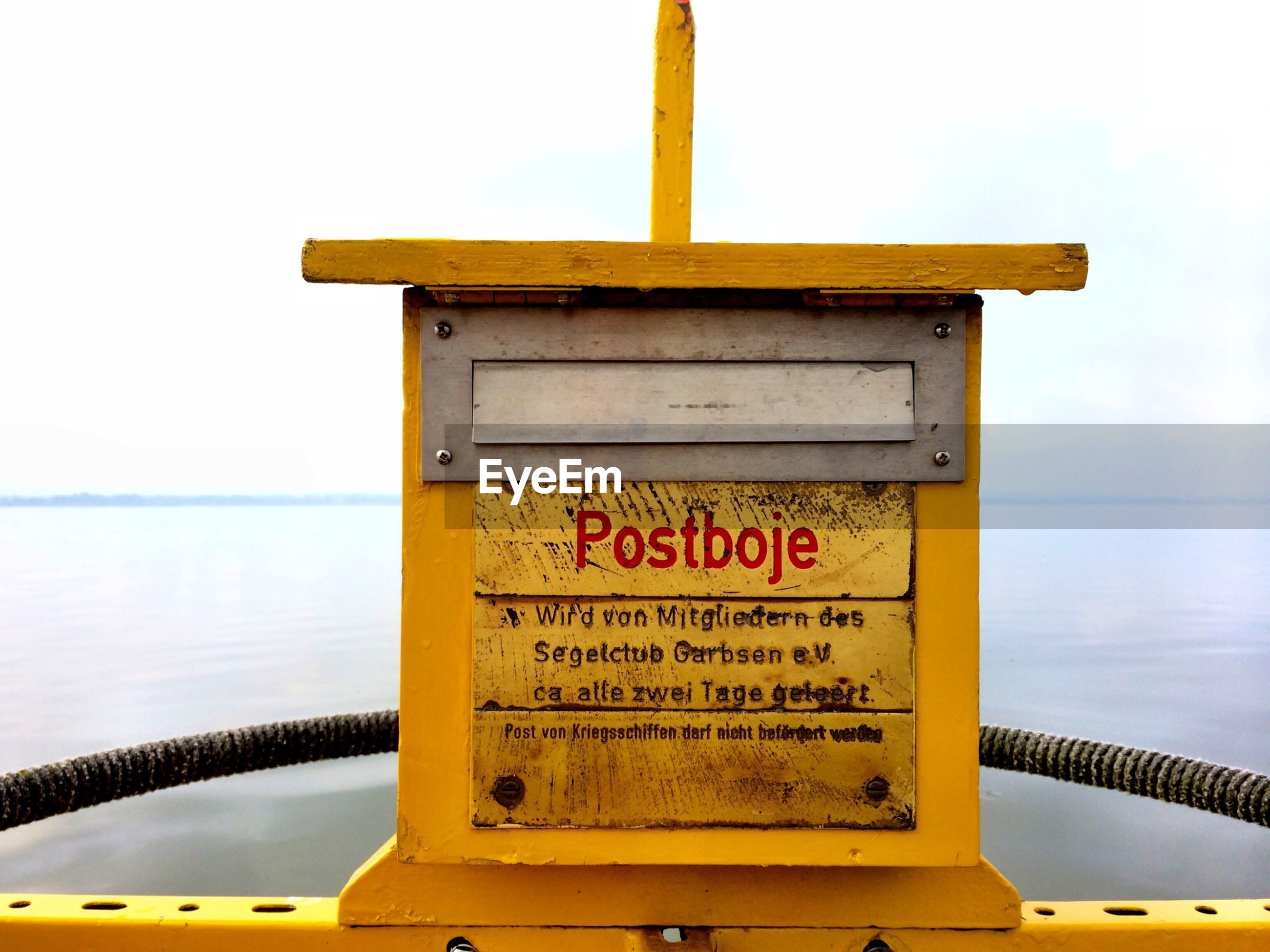 text, sea, water, western script, communication, yellow, horizon over water, warning sign, information sign, sky, guidance, transportation, railing, sign, clear sky, sunset, nautical vessel, non-western script, nature, capital letter