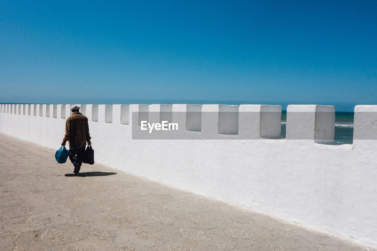 Man Walking On Road Against Clear Blue Sky