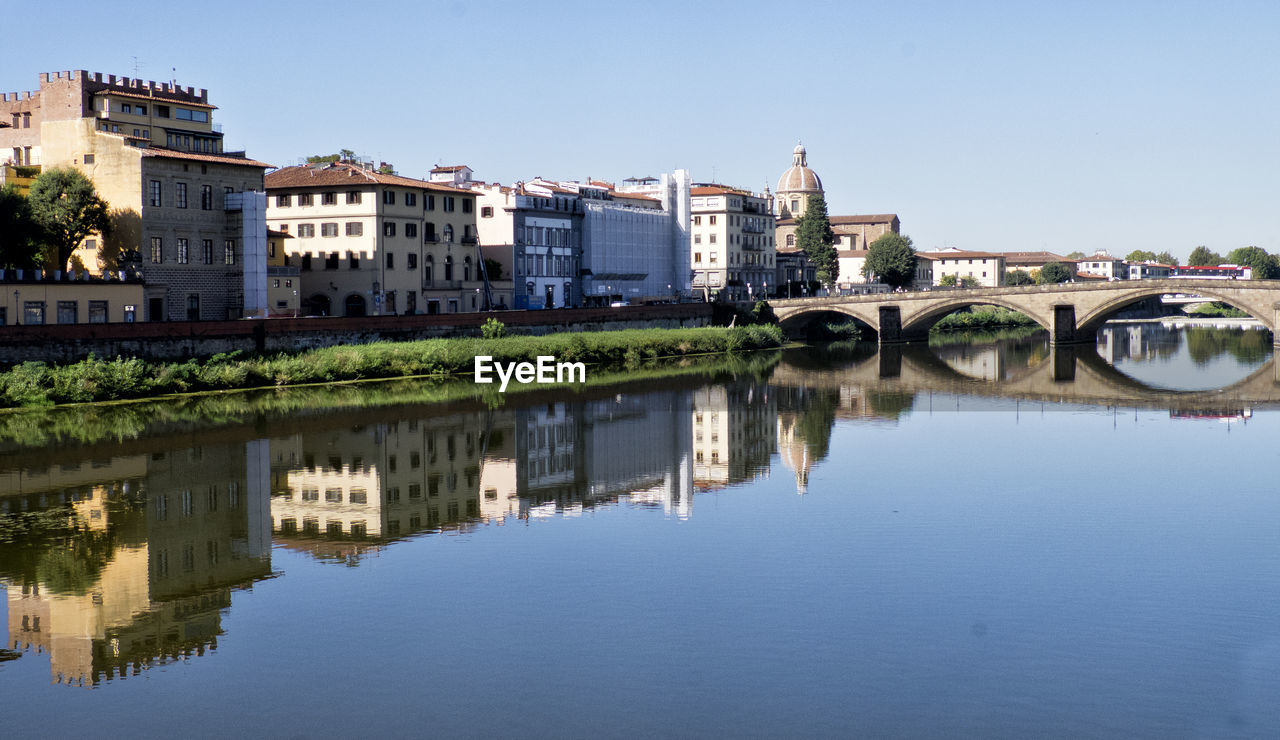 Reflection Of Buildings And Bridge On Arno River Against Sky