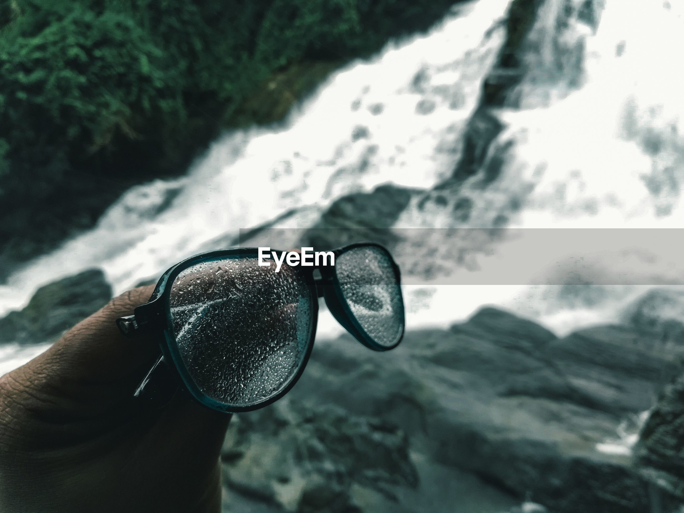 Cropped hand holding eyeglasses against waterfall